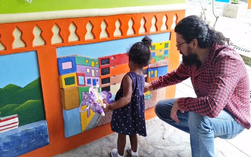 man showing toddler artwork on the wall