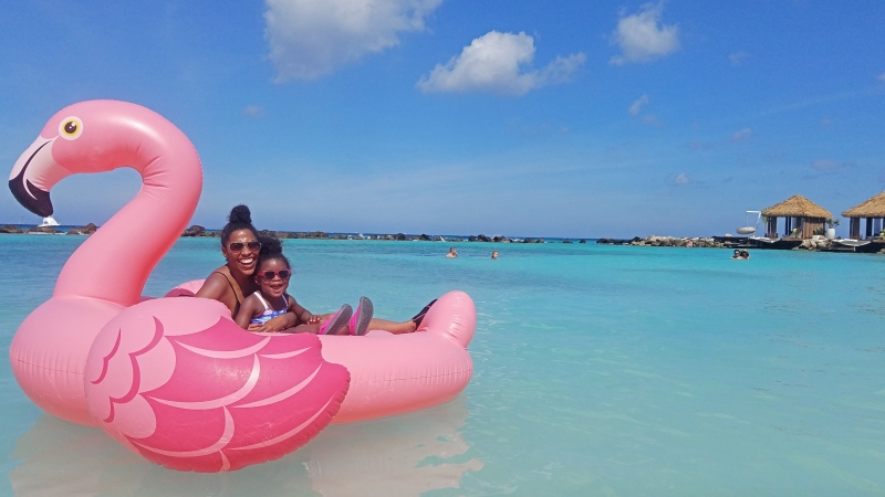 mom and daughter sitting in a flamingo floaty in the ocean