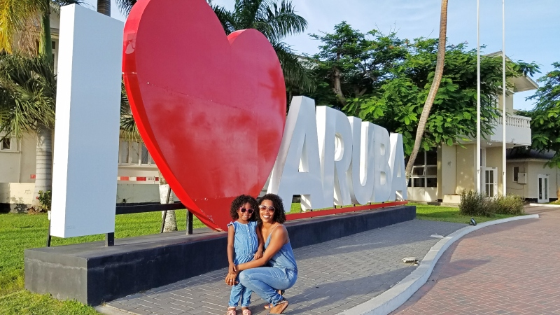 mom and daughter standing in front of I love Aruba sign