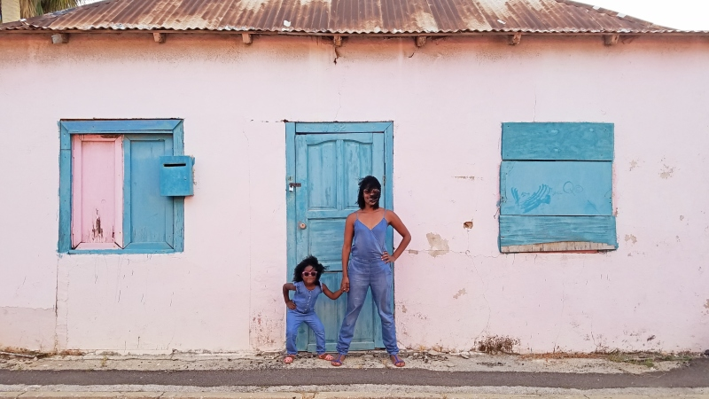 mom and daughter in matching outfits posing in front of a pink and blue building