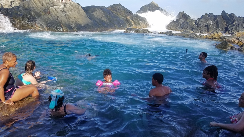 people in a natural pool in Aruba by the ocean