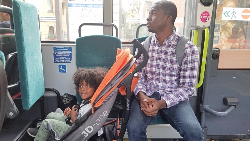 girl sitting in her stroller on the bus with her dad sitting next to her