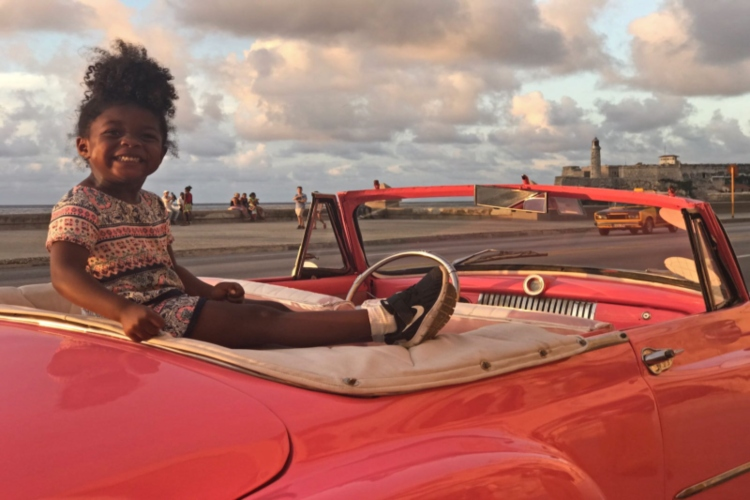 toddler sitting on the back of an open top classic car in cuba