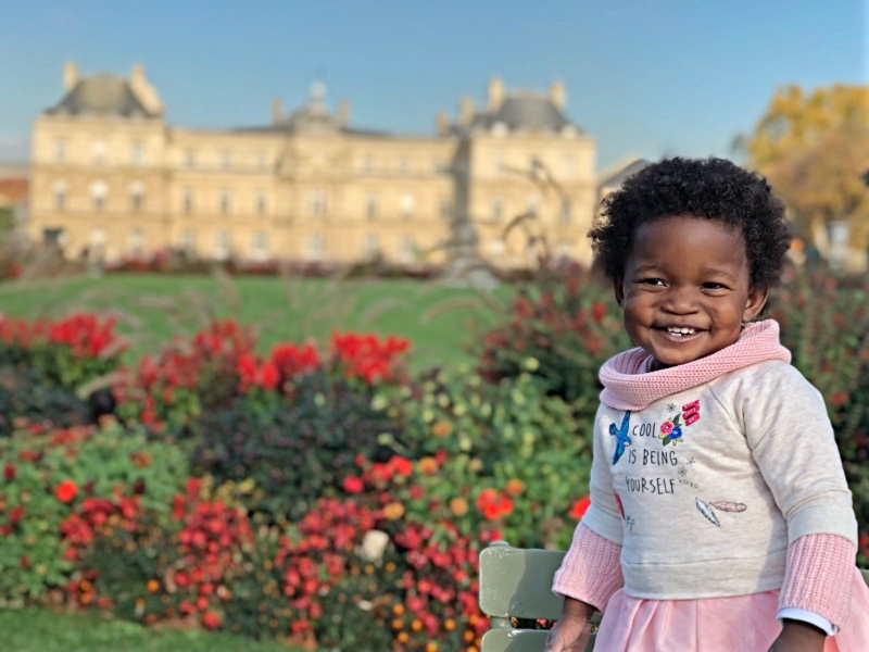 Toddler girl posing in garden in front of castle in Paris