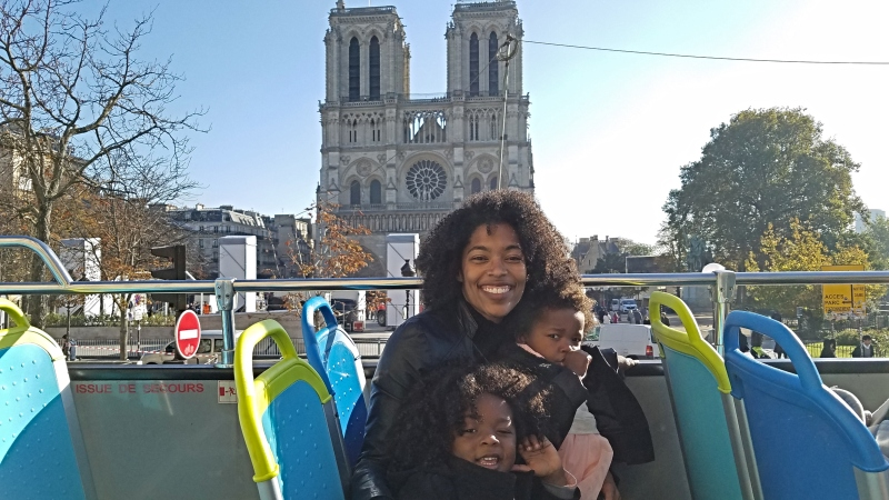 Mom and two daughters sitting on top of a hop on hop off bus in fron of the Notre Dame in Paris