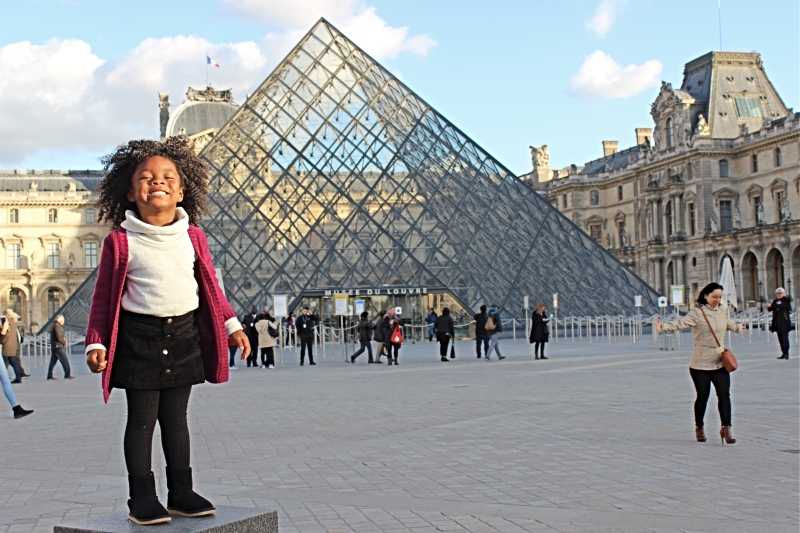 Girl standing in front of the pyramid at The Lourve in Paris