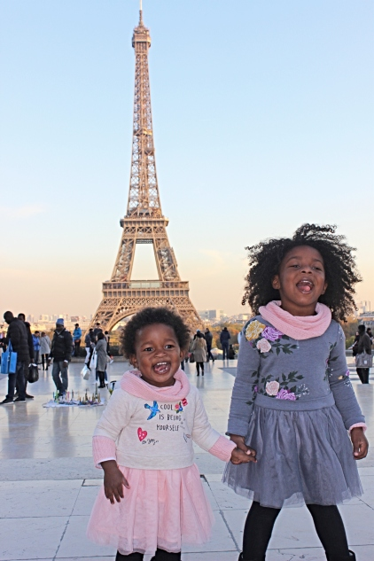 two toddler girls standing in front of the Eiffel Tower