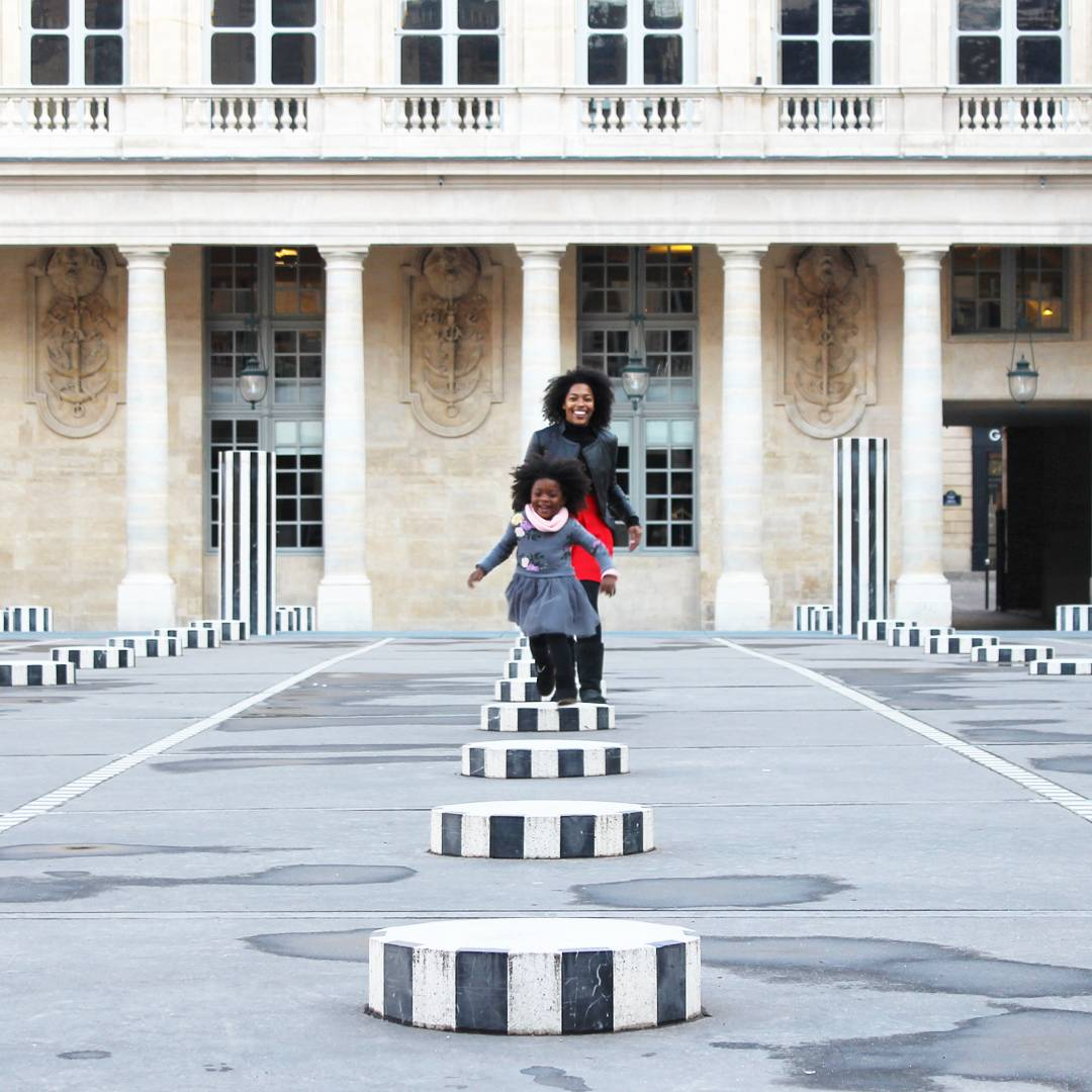 mother and daughter running in a courtyard in Paris