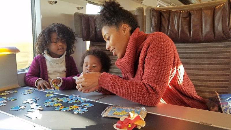 Mom doing a puzzle with her kids on a train