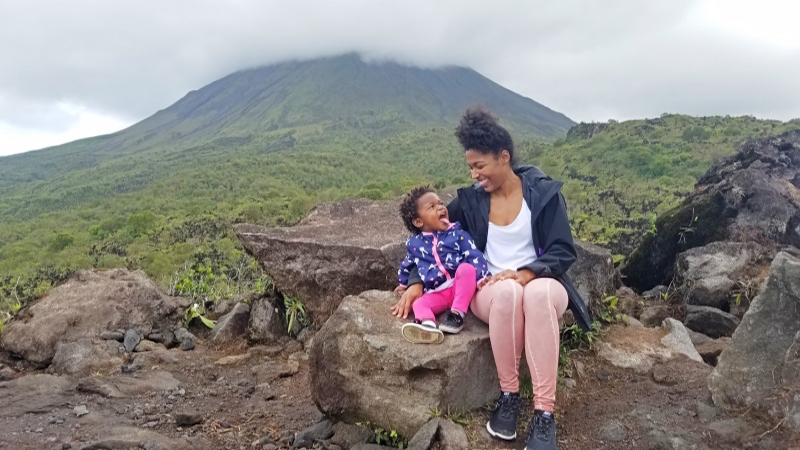 mom and daughter sitting on rock with the Arenal volcano in the back