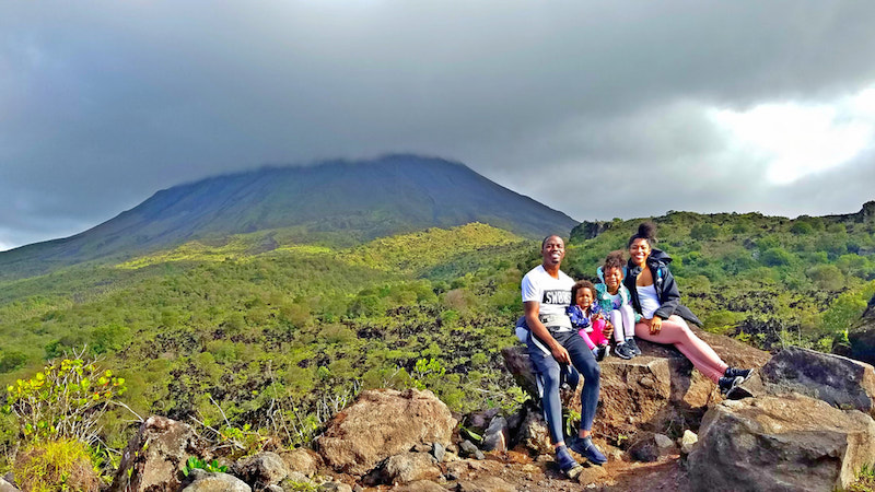 family sitting down on rock with a volcano in the background