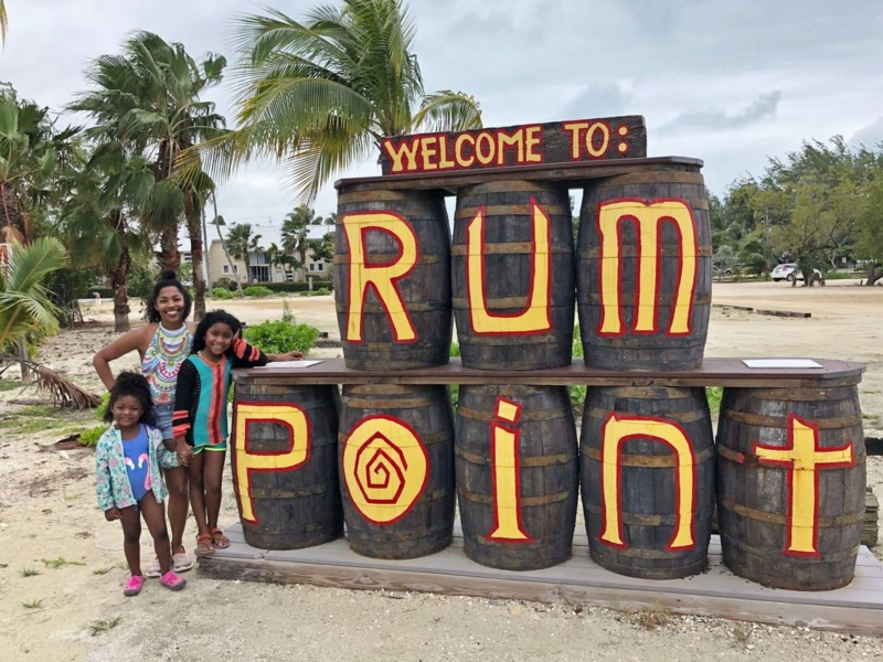 three girls standing next to Welcome to Rum Point sign