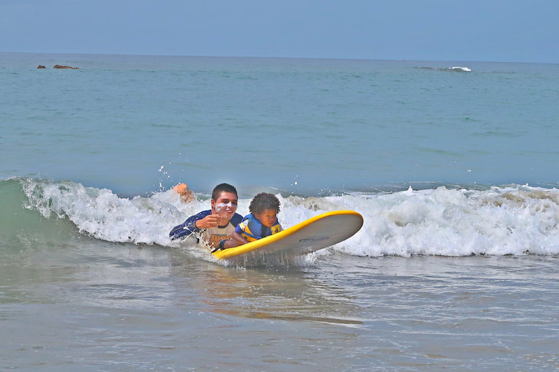 little girl surfing with her instructor
