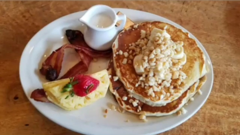 plate with pancakes, bacon and pineapples