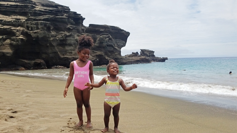 two young black girls on the beach in hawaii