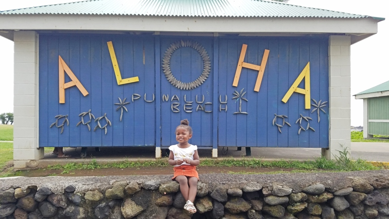 Little girl sitting on a wall in front of a sign that says Aloha