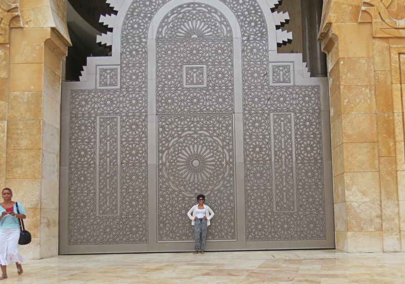 women standing in front of a beautiful door at a mosque