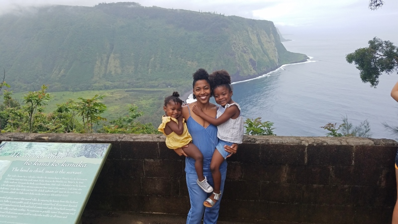 mom holding two young daughters with beautiful cliff in the background