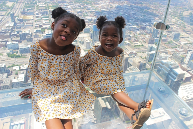 two young girls sitting on a glass floor with views to the bottom of the street