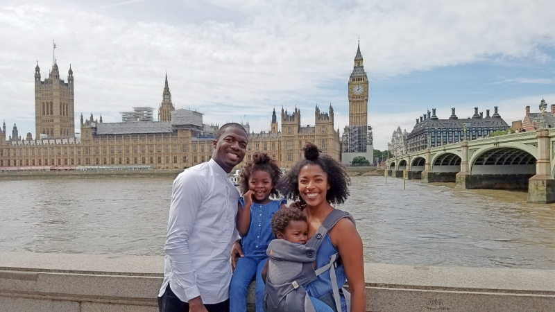 young black family of four standing in front of big ben
