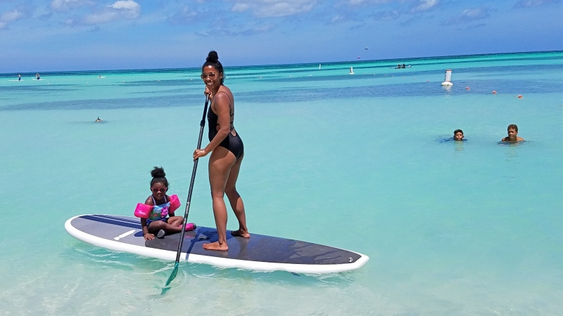 mom on stand up paddle board with her toddler