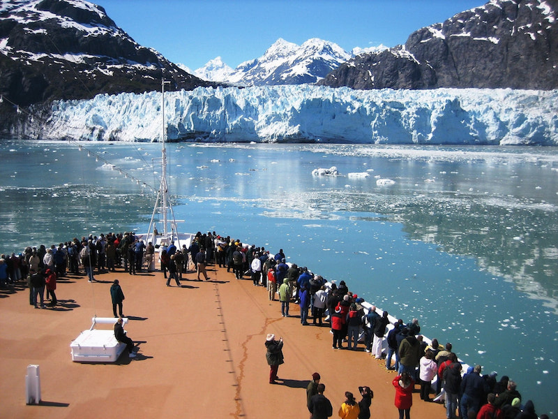 cruise ship with passengers looking at glaciers in the ocean