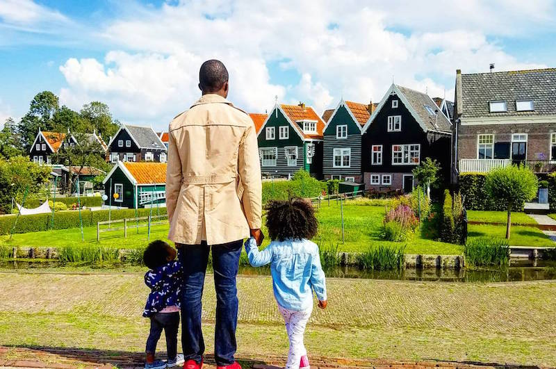 dad holding little daughters hands looking at colorful houses in a neighborhood