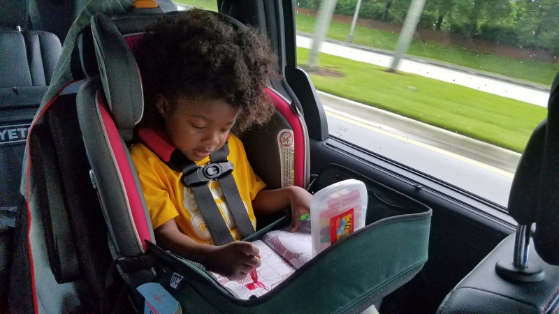 toddler girl coloring on a road trip