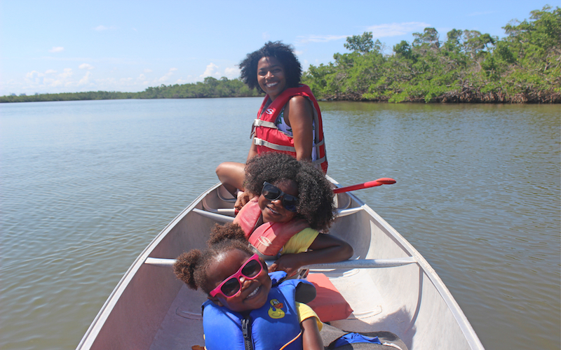 mom and two toddler daughters canoeing