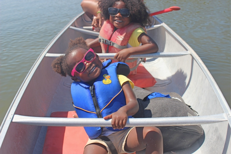little girls smiling in a canoe