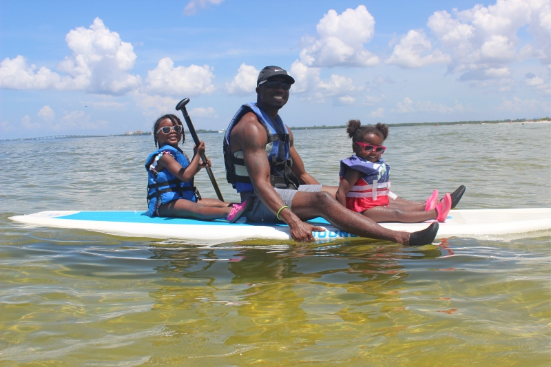 dad on paddle board with two daughters