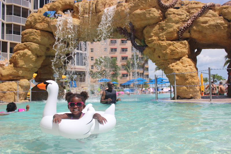 little girl in swan floaty in the pool