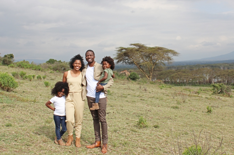 black family standing in a game reserve in Kenya with giraffes in the background