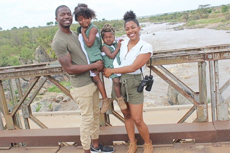 black family standing on a bridge in front of the Mara River in Kenya