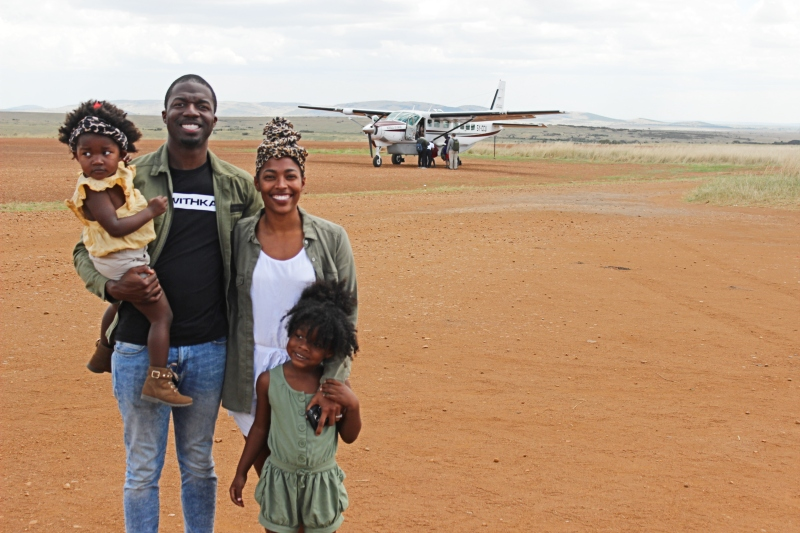 family standing on an airstrip in front of a tiny plane