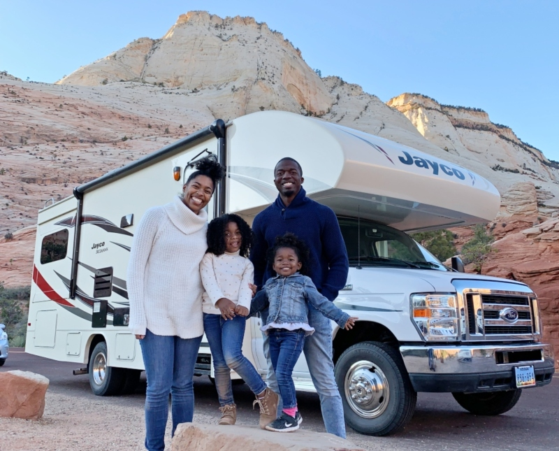 family standing in front of RV on their southwest road trip