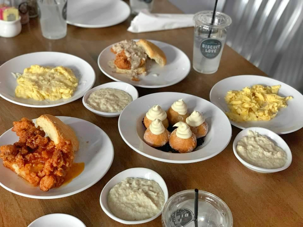 a table filled with food from Biscuit Love including bonuts, chicken sandwiches, eggs, and grits