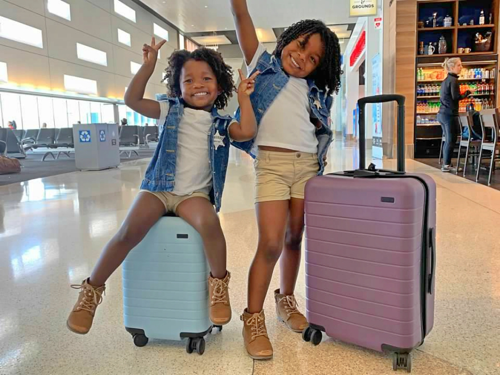 Two black children sitting on suitcases at the airport