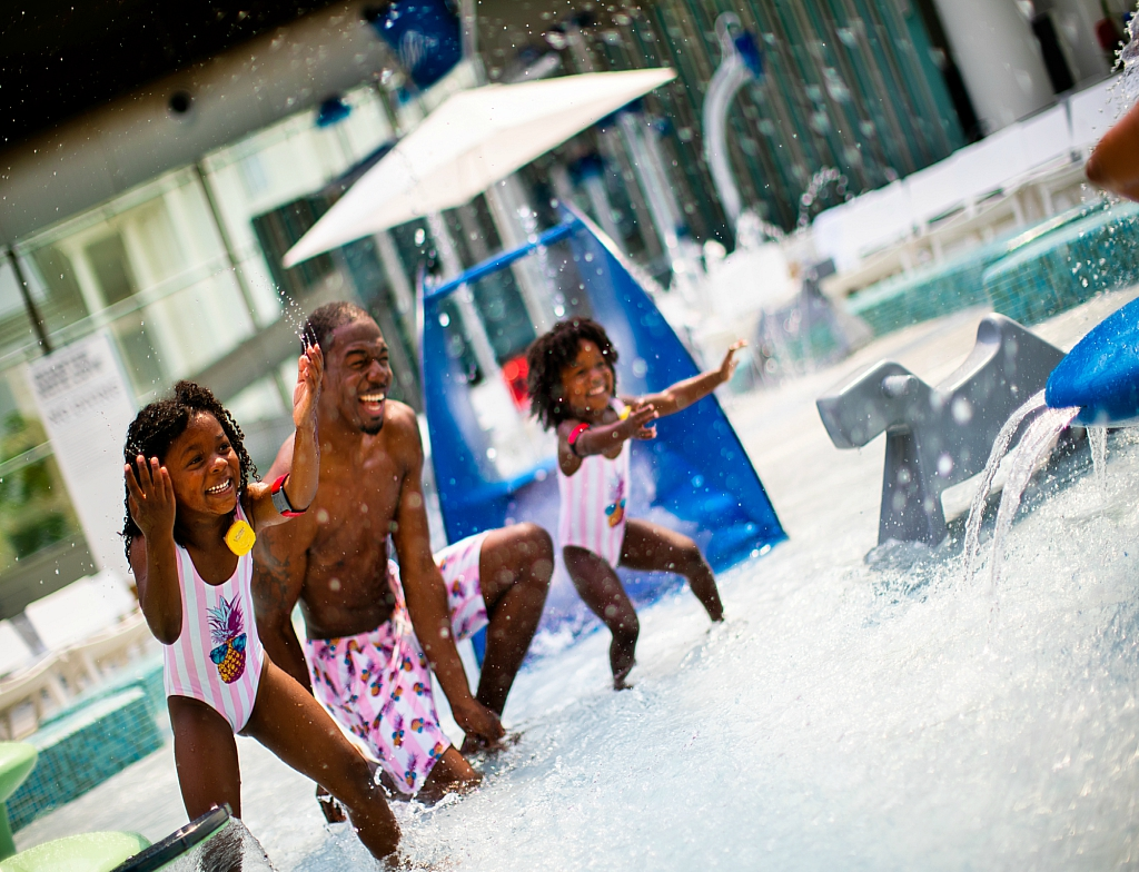Black father splashing water in the pool with his daughters