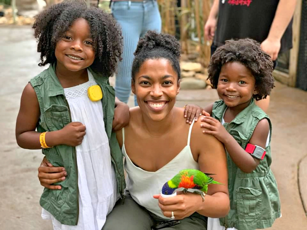 Black Family enjoying the Lorikeet Exhibit where the mom is feeding the lorikeet and her daughters and standing next to her