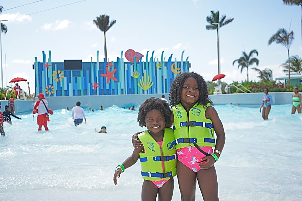 two girls standing in front of a wave pool with life vests on