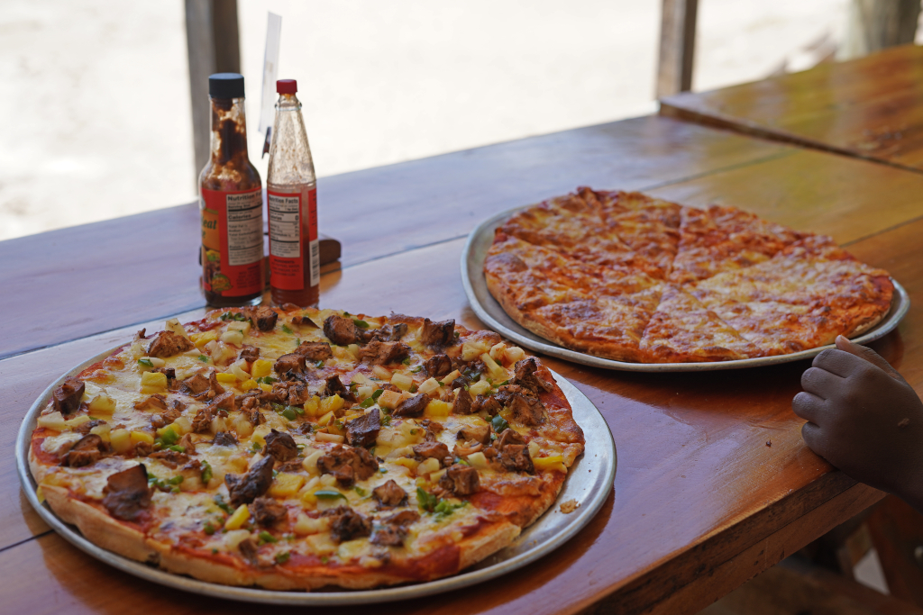 two pizzas sitting on a wooden table