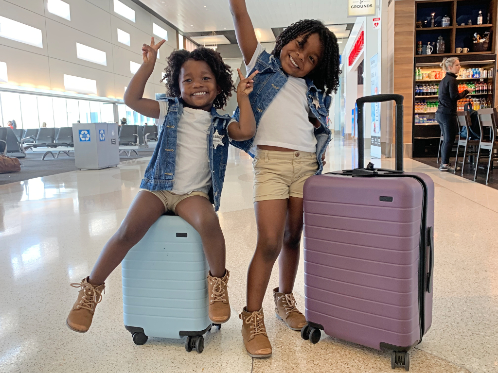 two toddlers with suitcases