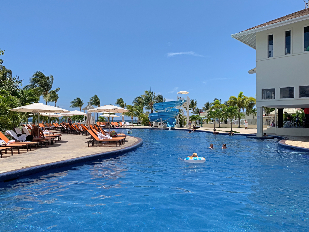 resort pool with orange pool chairs and a blue water slide