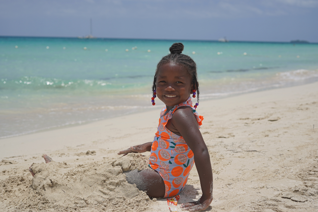 Little girl sitting on the beach in Negril, Jamaica with sand covering her legs