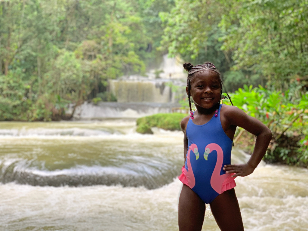 girl standing in front of waterfall in Jamaica