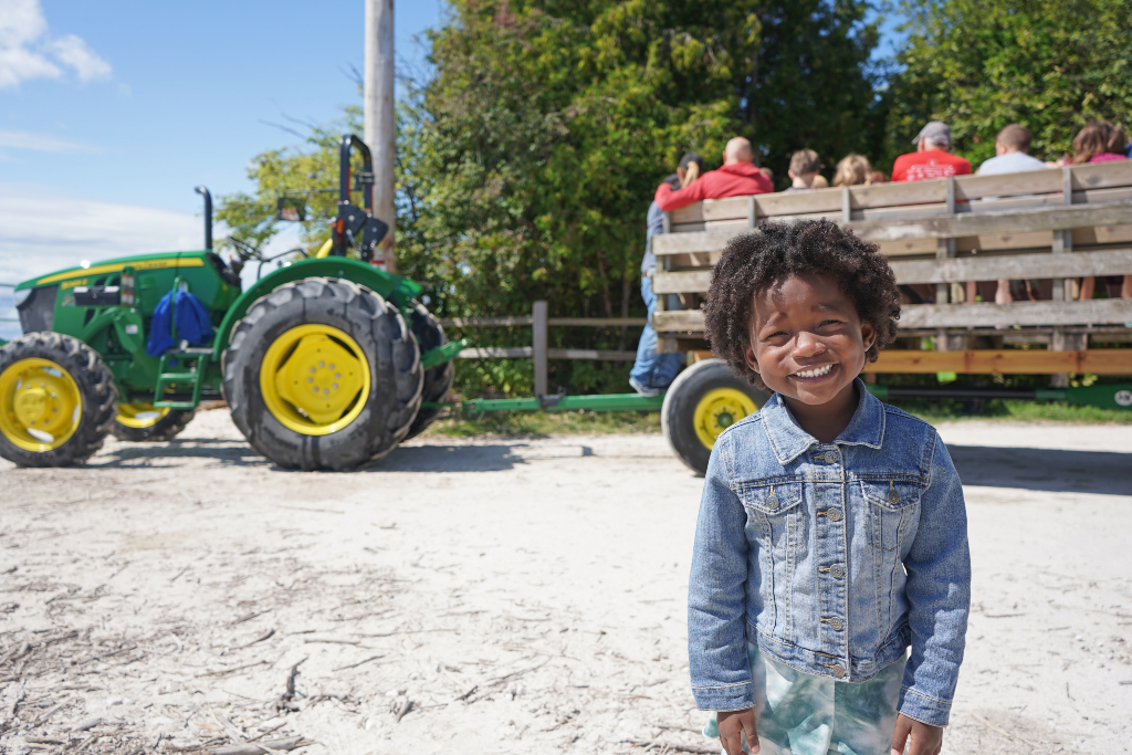 Little girl smiling at the camera with a tractor and pull behind her.