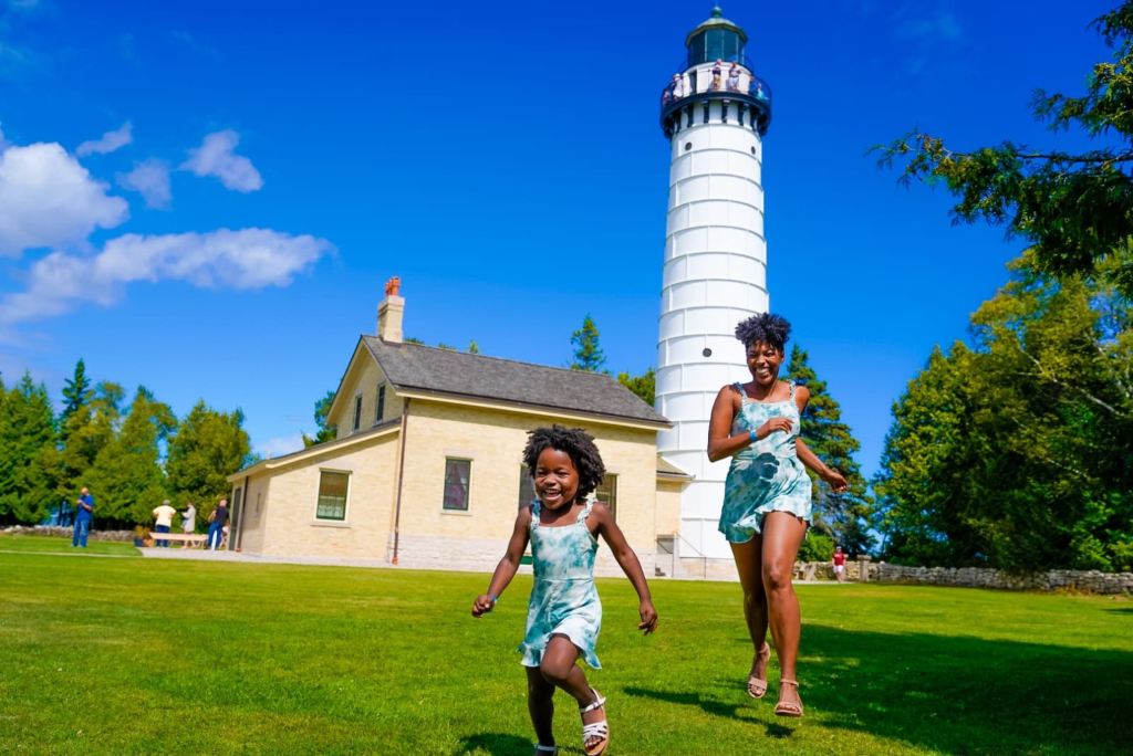 Cana island lighthouse a Mom and daughter running through the grass.