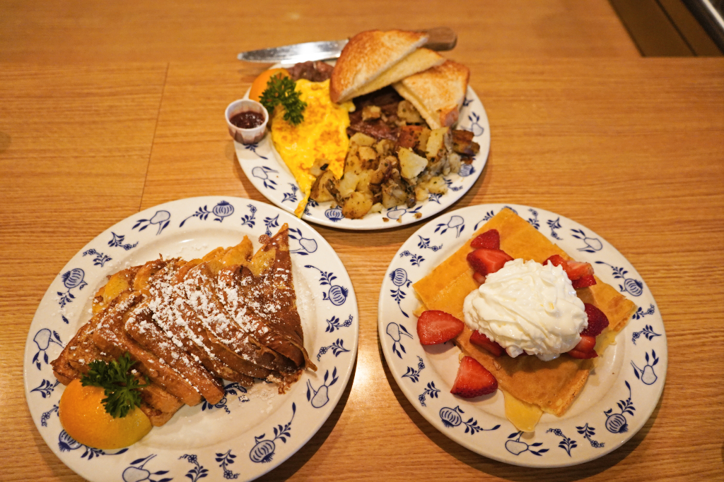3 plates of food including french toast, swedish pancakes, and eggs and potatoes.
