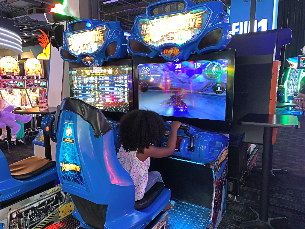 girl playing games at arcade